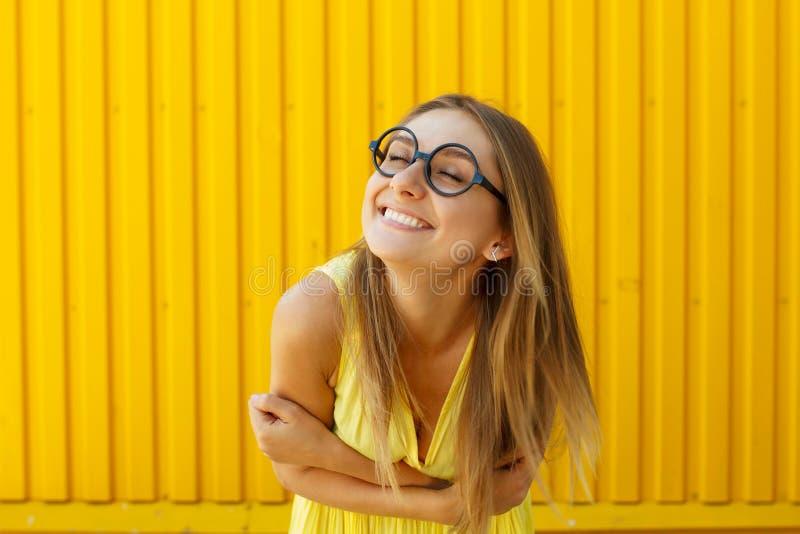 Schöne junge Frau in den lustigen Spielzeuggläsern lächelnd über gelbem b stockbilder