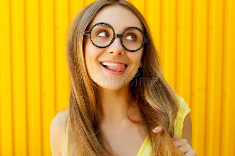 Schöne junge Frau in den lustigen Spielzeuggläsern lächelnd und t zeigend lizenzfreie stockfotos