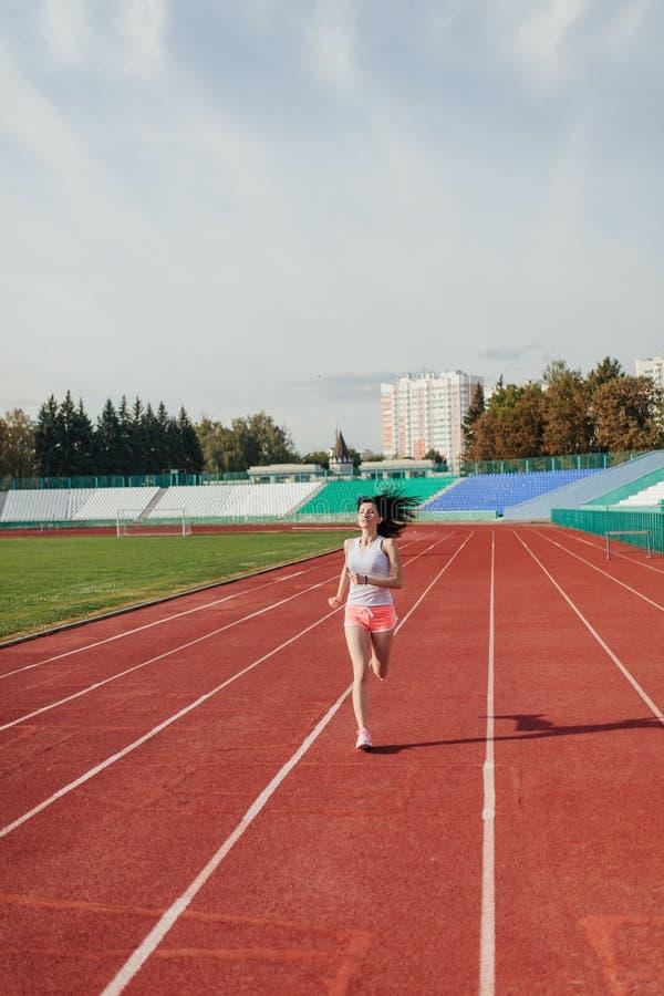 Schöne junge Frau in den rosa kurzen Hosen und im Behälter, zum des Rüttelns und des Laufens auf athletischer Bahn auf Stadion be stockbild