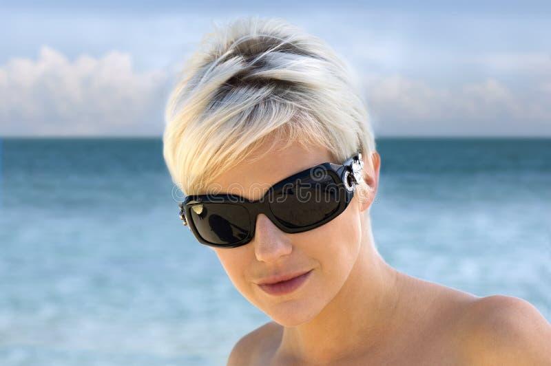 Schöne junge Frau in den Sonnenbrillen lizenzfreie stockbilder