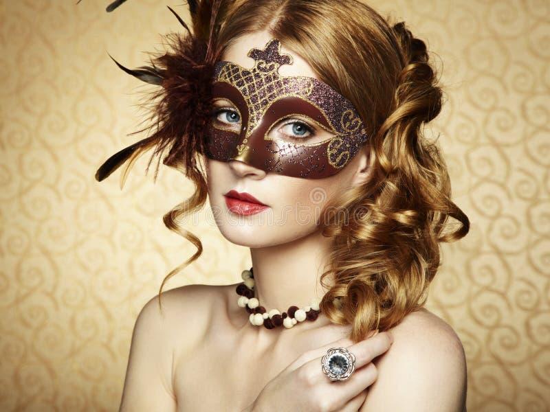 Schöne junge Frau in der braunen venetianischen Schablone stockfoto