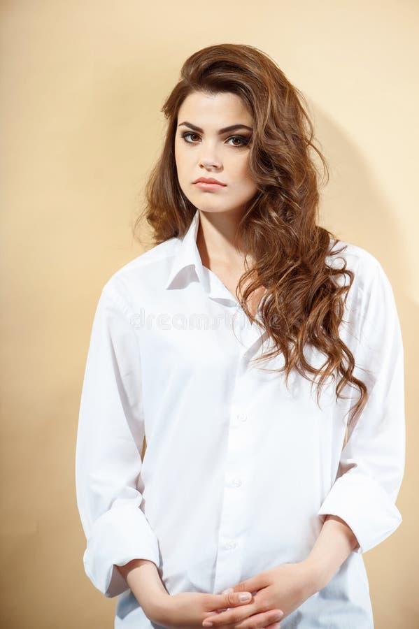 Schöne junge Frau in der breiten weißen Bluse stockfoto