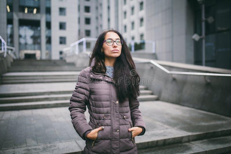 Schöne junge Frau der europäischen Ethnie mit dem langen Brunettehaar, den tragenden Gläsern und einem Mantel steht gegen Hinterg stockfoto