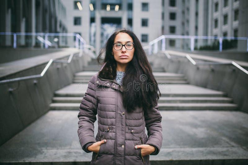 Schöne junge Frau der europäischen Ethnie mit dem langen Brunettehaar, den tragenden Gläsern und einem Mantel steht gegen Hinterg lizenzfreies stockfoto