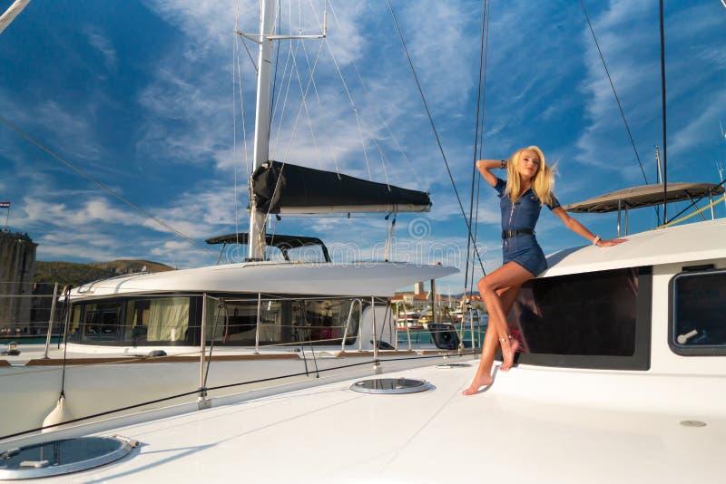 Schöne junge Frau in der Freizeitkleidung, die auf einem Yachtvorderteil an Trogir-Jachthafen, Kroatien steht lizenzfreie stockfotos