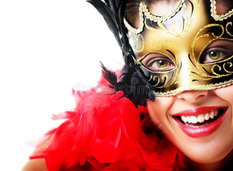 Schöne junge Frau in der Karnevalsschablone und -feder stockfoto