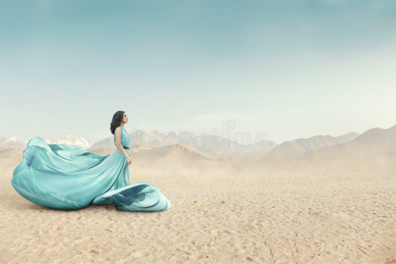 Schöne junge Frau in der langen flatternden Kleideraufstellung im Freien stockfoto