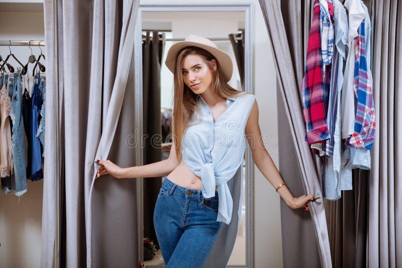 Schöne junge Frau in der Umkleidekabine des Kleidungsshops lizenzfreies stockbild