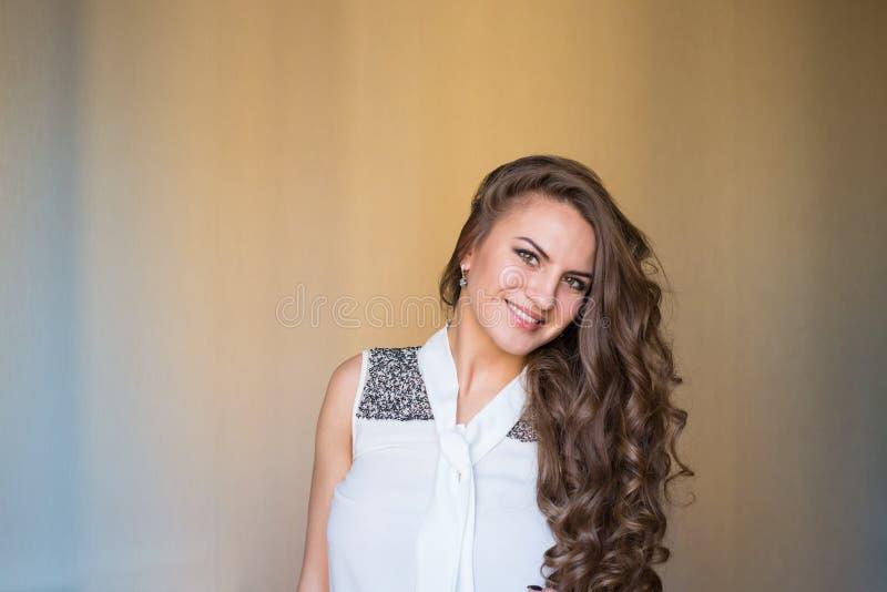 Schöne junge Frau in der weißen Bluse mit gesundem braunem gelocktem h lizenzfreies stockfoto