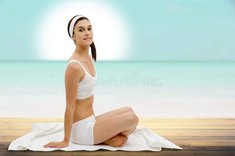 Schöne junge Frau in der weißen Unterwäsche, die auf Tuch sitzt lizenzfreie stockbilder