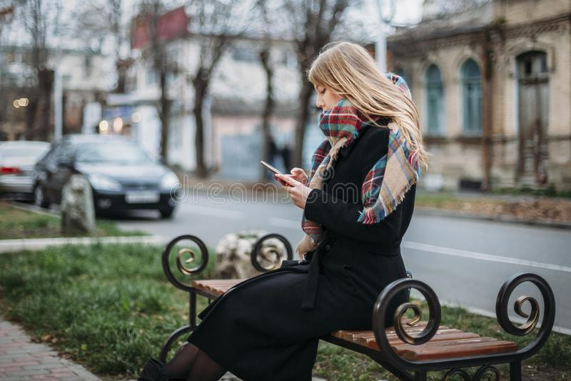 Schöne junge Frau des Porträts auf Bank im städtischen Hintergrund, der Telefon schaut lizenzfreie stockbilder