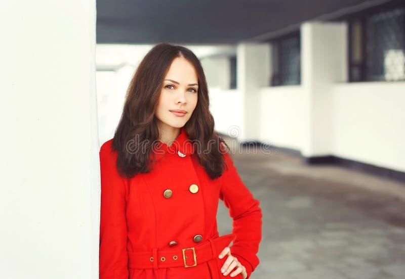 Schöne junge Frau des Porträts, die einen roten Mantel trägt stockfotos