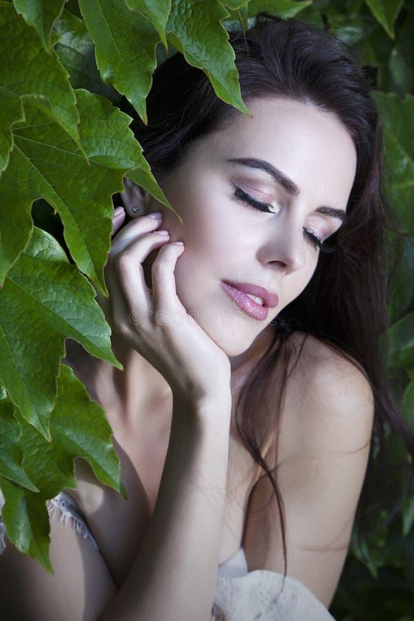 Schöne junge Frau des Porträts mit geschlossenen Augen in den grünen Blättern von wilden Trauben lizenzfreie stockbilder