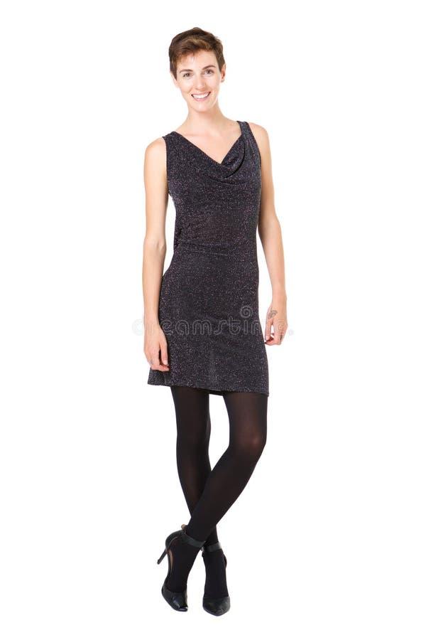 Schöne junge Frau des vollen Körpers mit dem kurzen Haar im schwarzen Kleid gegen lokalisierten weißen Hintergrund lizenzfreie stockbilder