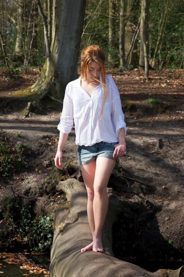 Schöne junge Frau, die über einen Klotz über Strom geht lizenzfreies stockfoto