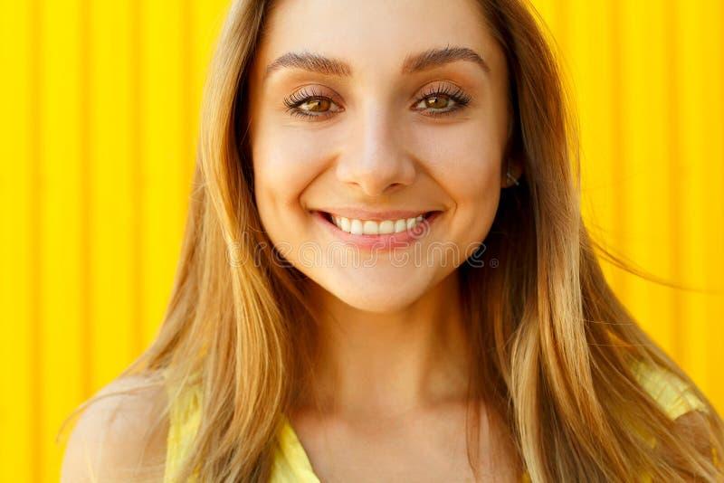 Schöne junge Frau, die über gelbem Hintergrund am Tageslicht lächelt lizenzfreies stockfoto