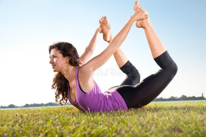Schöne junge Frau, die Übung auf grünem Gras ausdehnend tut. stockbild