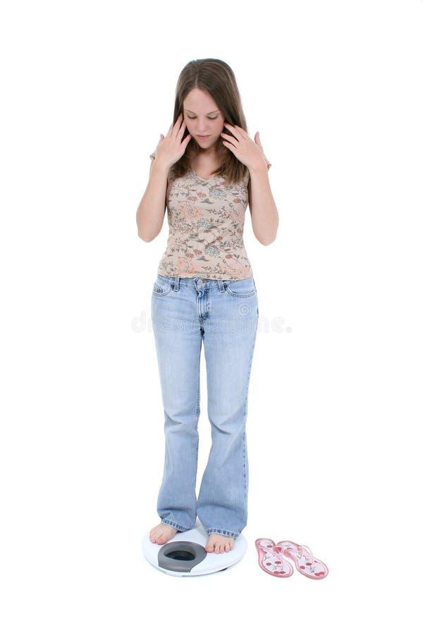 Schöne junge Frau, die auf Badezimmer-Skala steht stockbilder
