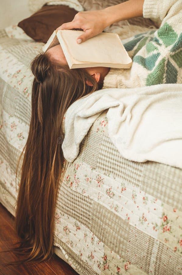 Schöne junge Frau, die auf Bett mit dem Buch bedeckt ihr Gesicht weil Ablesenbuch mit dem Vorbereiten der Prüfung des Colleges sc lizenzfreie stockbilder