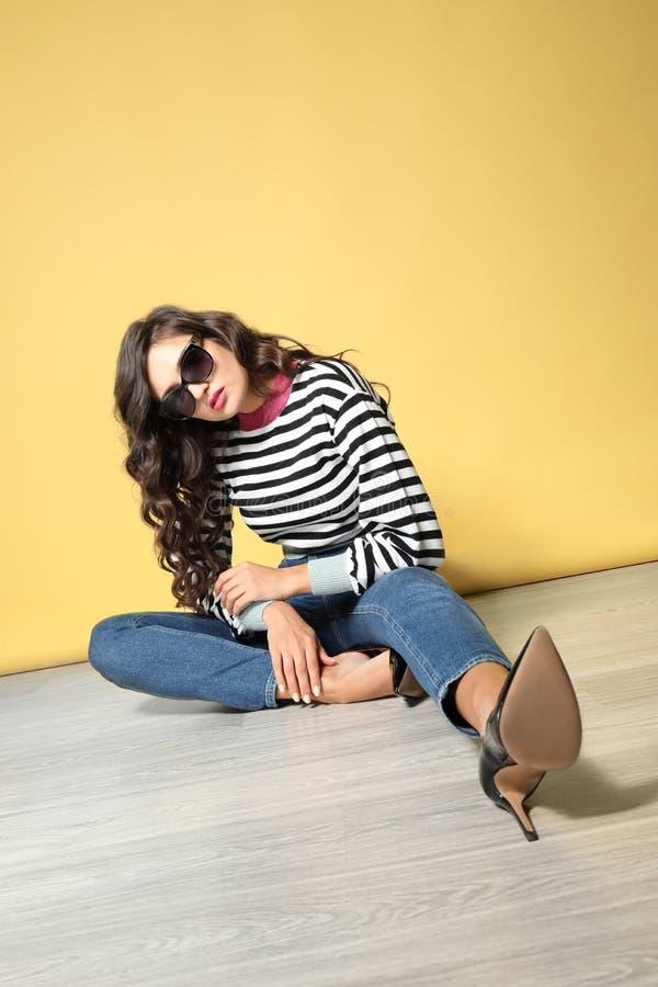 Schöne junge Frau, die auf Boden nahe Farbhintergrund sitzt lizenzfreie stockfotos