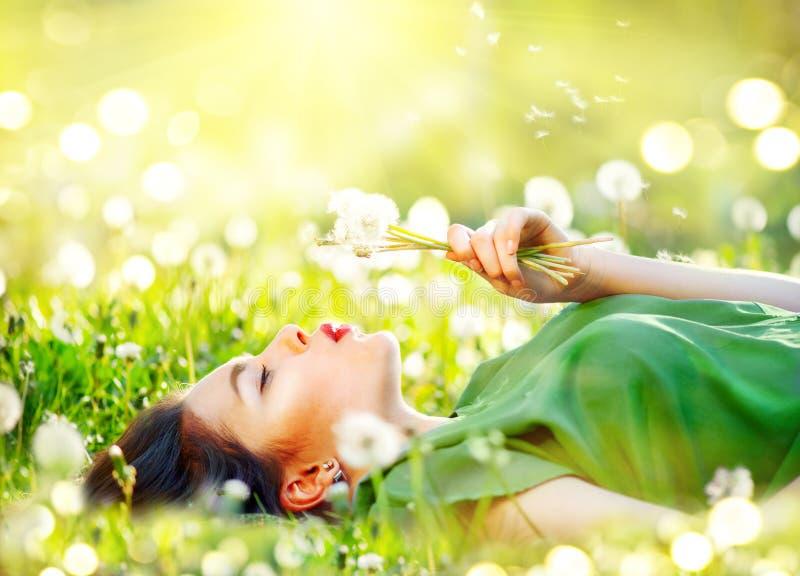 Schöne junge Frau, die auf dem Feld im grünen Gras und in Schlaglöwenzahnblumen liegt stockbilder