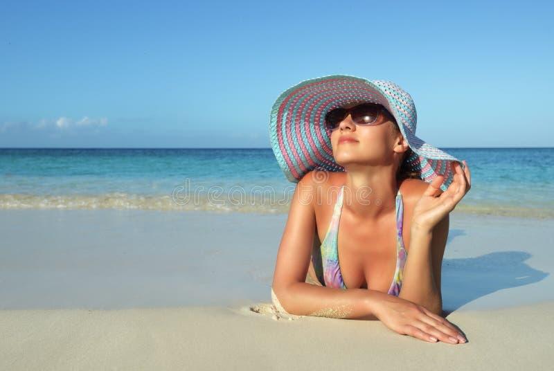 Schöne junge Frau, die auf dem Strandträumen liegt stockbilder