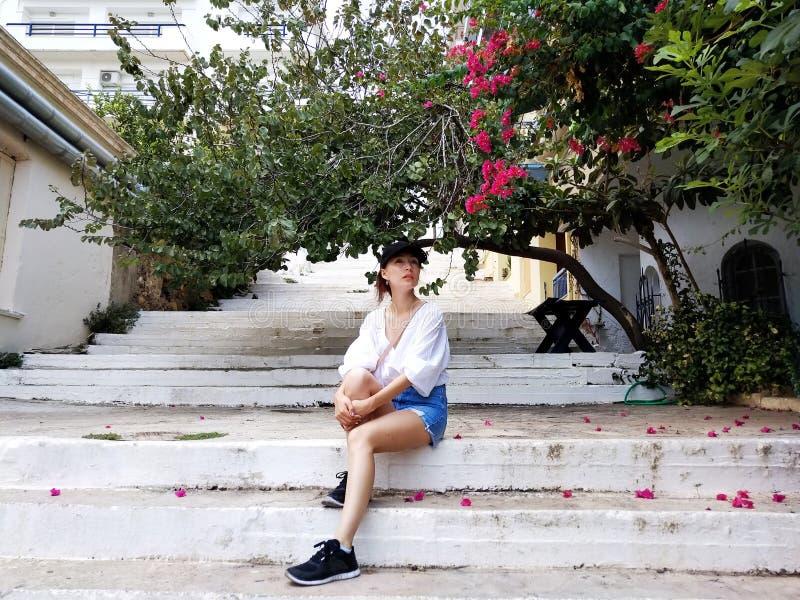 Schöne junge Frau, die auf der alten Straße von Agios Nikolaos, Kreta, Griechenland sitzt Blühender Baum des Bouganvillas lizenzfreie stockfotos