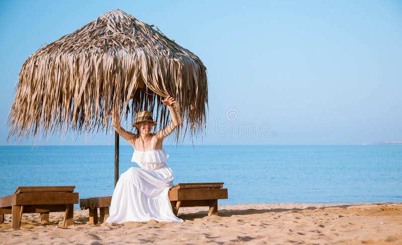 Schöne junge Frau, die auf der Bank auf dem Strand sitzt stockfoto