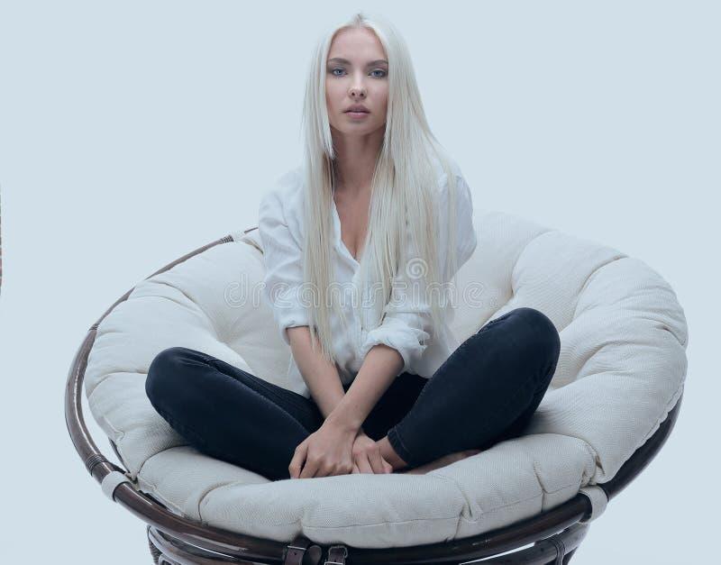 Schöne junge Frau, die auf der Couch in einem großen bequemen Lehnsessel sitzt lizenzfreie stockfotos