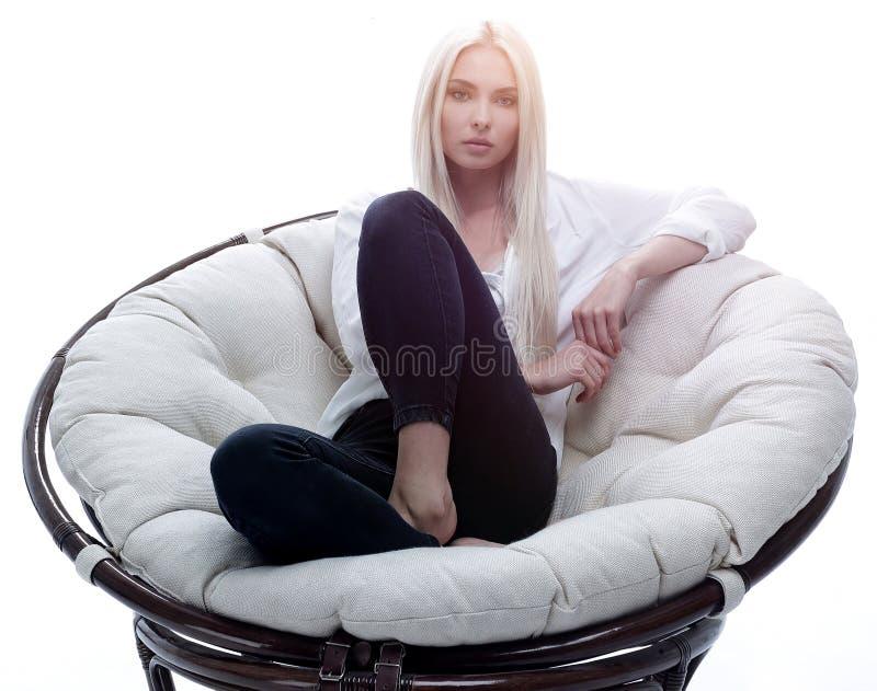 Schöne junge Frau, die auf der Couch in einem großen bequemen Lehnsessel sitzt stockbild
