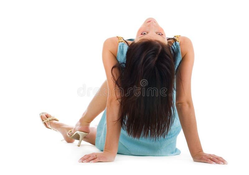 Schöne junge Frau, die auf einem Fußboden sitzt lizenzfreie stockfotografie