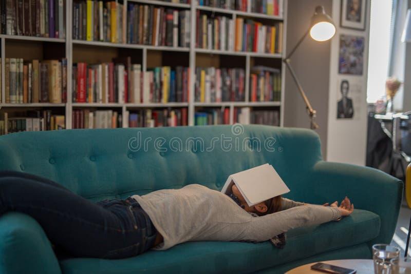 Schöne junge Frau, die auf einer Couch in einer Bibliothek mit einem Buch liegt lizenzfreie stockfotografie