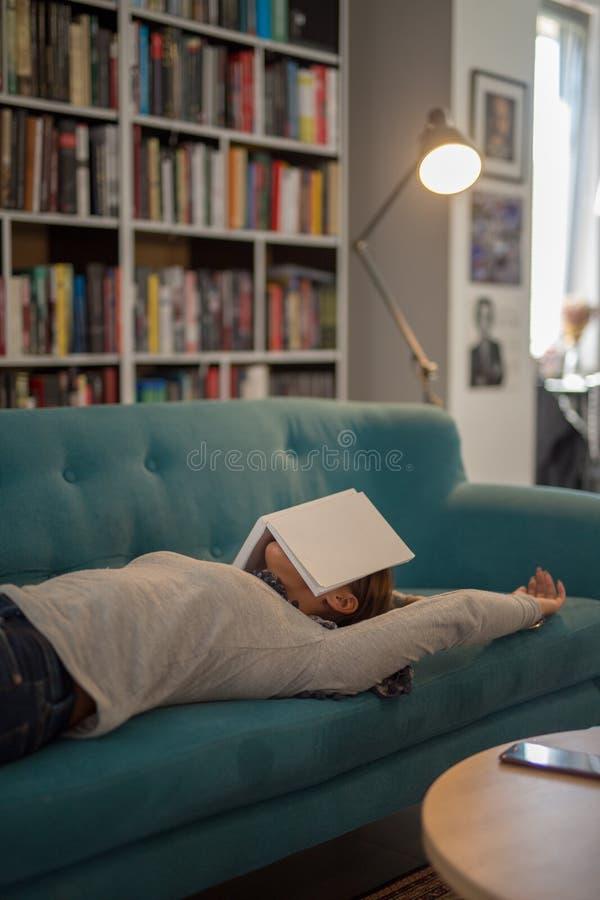 Schöne junge Frau, die auf einer Couch in einer Bibliothek mit einem Buch liegt lizenzfreie stockbilder