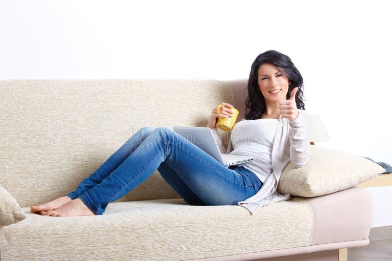 Schöne junge Frau, die auf Sofa sich entspannt lizenzfreie stockfotografie