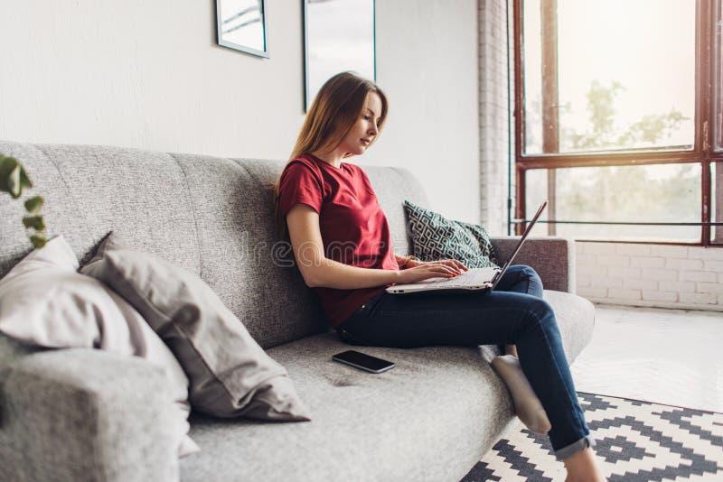 Schöne junge Frau, die auf Sofa sitzt und zu Hause Laptop verwendet stockfotografie