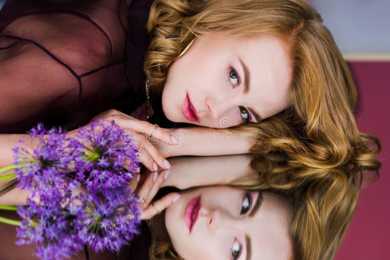 schöne junge Frau, die auf Spiegel mit blauen Blumen und dem Schauen liegt lizenzfreies stockbild