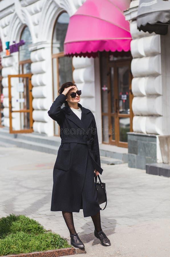 Schöne junge Frau, die auf die Straße tut das Einkaufen geht stockfoto