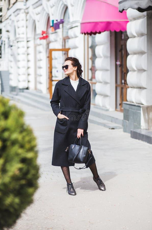 Schöne junge Frau, die auf die Straße tut das Einkaufen geht lizenzfreie stockfotografie