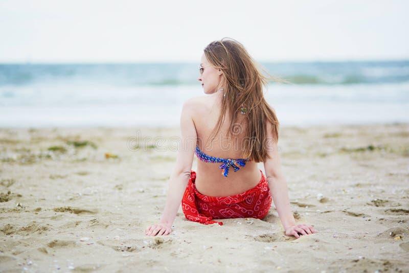 Schöne junge Frau, die auf Strand sich entspannt und ein Sonnenbad nimmt stockfotografie