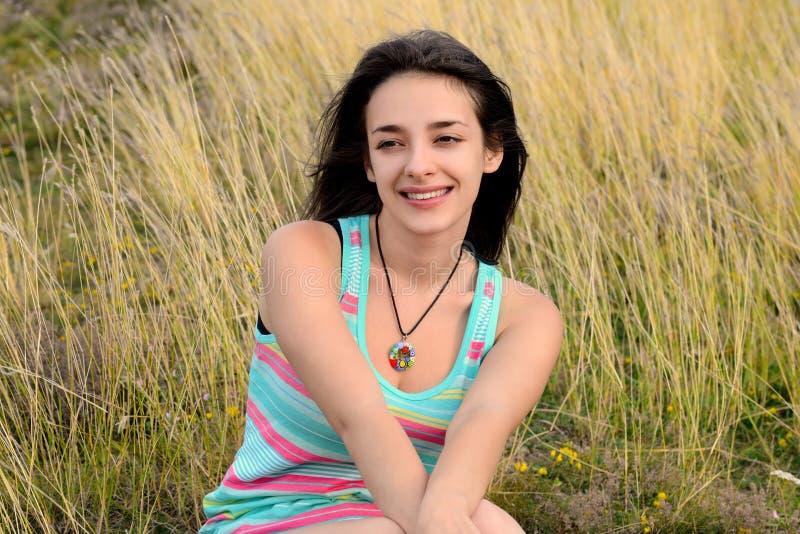 Schöne junge Frau, die auf trockenem Gras sitzt stockbilder