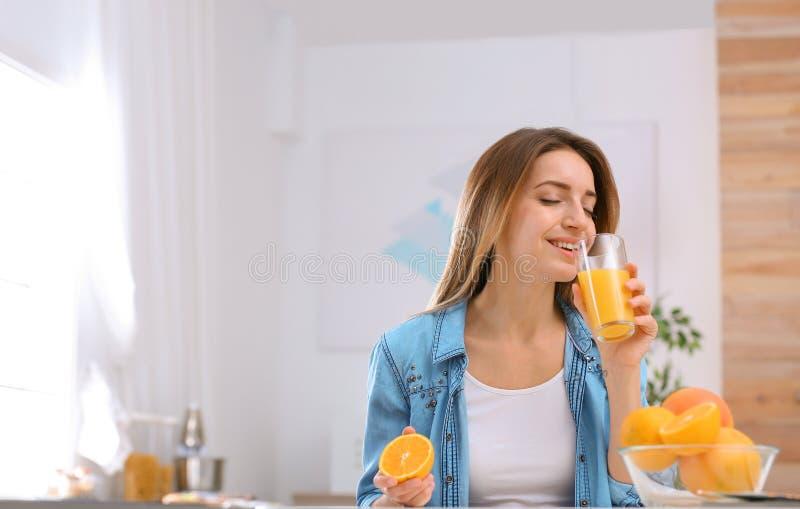 Schöne junge Frau, die bei Tisch Orangensaft zuhause, Raum für Text trinkt stockbild