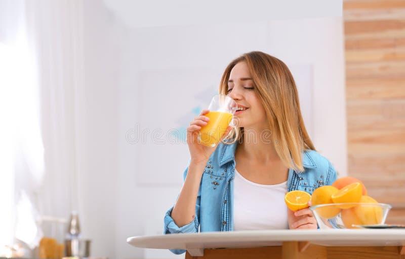Schöne junge Frau, die bei Tisch Orangensaft zuhause, Raum für Text trinkt stockbilder