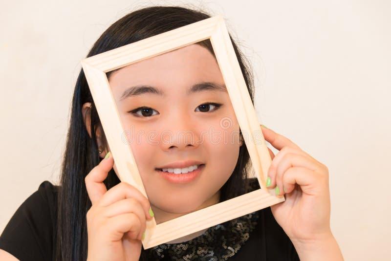 Schöne junge Frau, die Bilderrahmen anhält stockfotos