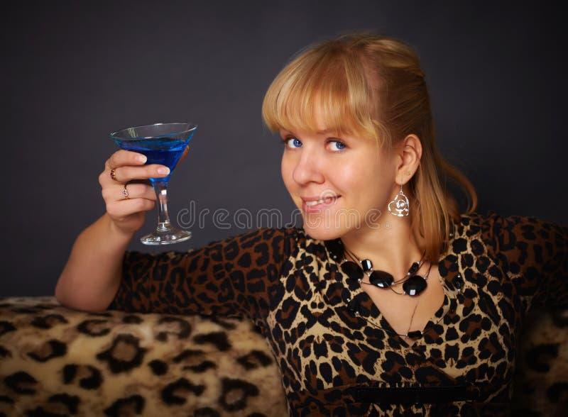 Schöne junge Frau, die blaues Cocktail trinkt stockfoto