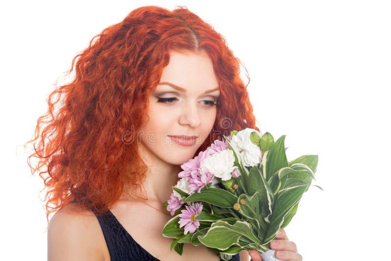 Schöne junge Frau, die Blumen betrachtet lizenzfreies stockfoto