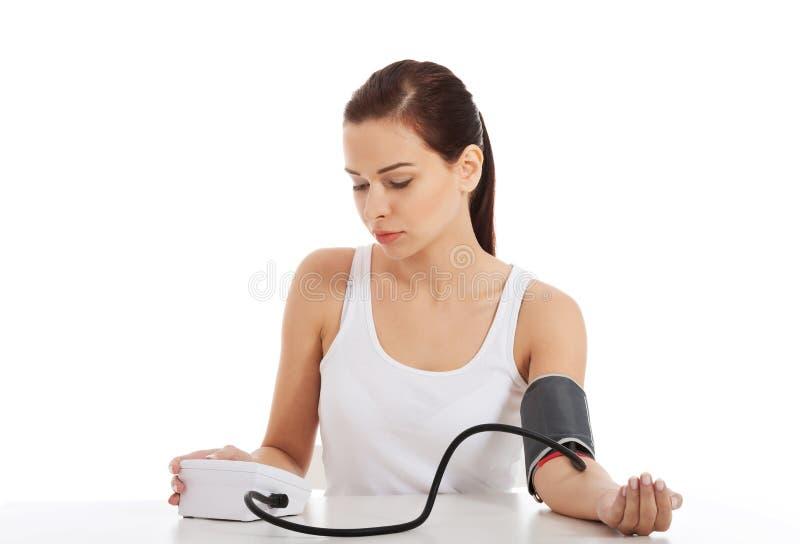 Schöne junge Frau, die Blutdrucktest macht. lizenzfreies stockbild