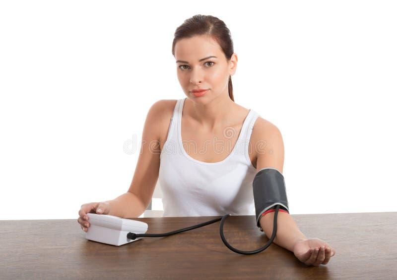 Schöne junge Frau, die Blutdrucktest macht. stockfotos