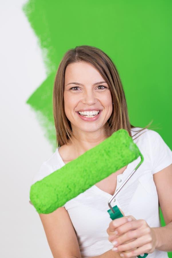 Schöne junge Frau, die das Haus malt lizenzfreies stockbild