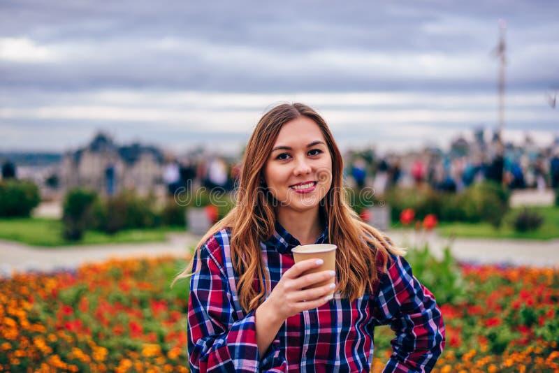 Schöne junge Frau, die das Kaffeetasse und Lächeln hält stockbild