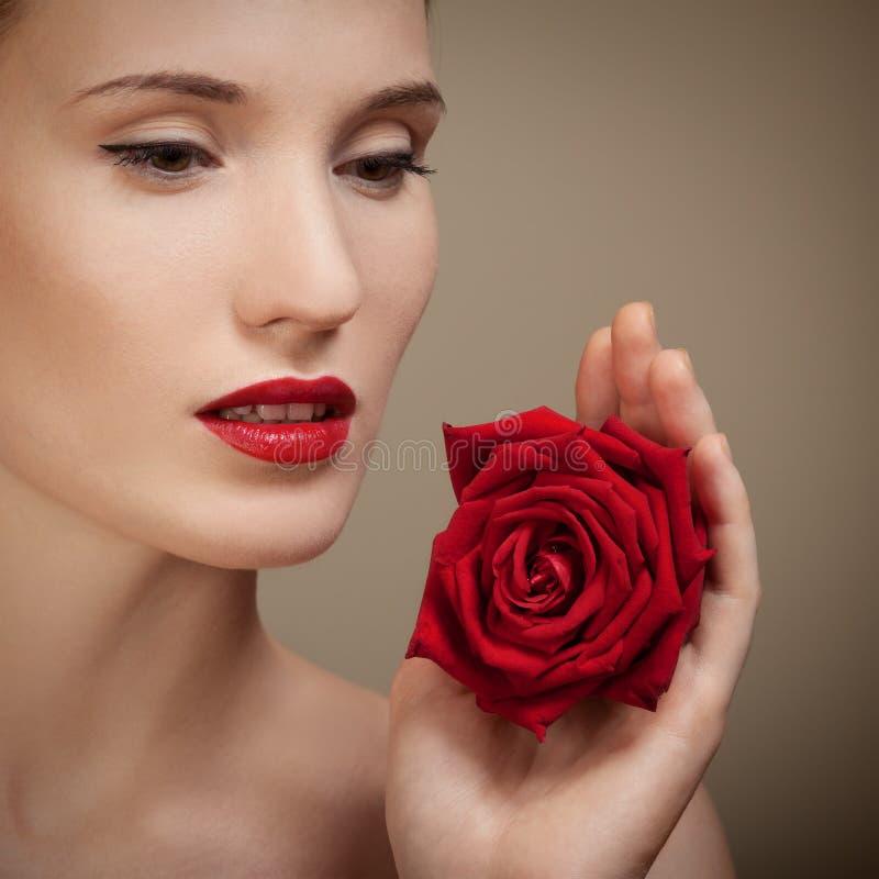 Schöne Frau, die in der Hand rote Rose hält stockbilder